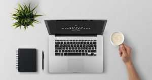 open laptop on desk with notepad, pen, and plant