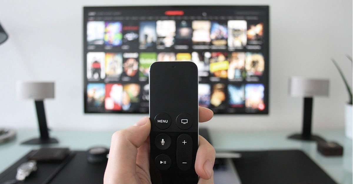 close up of hand holding remote in front of tv streaming movies
