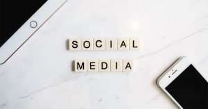 letter tiles that spall social media next to computer and phone