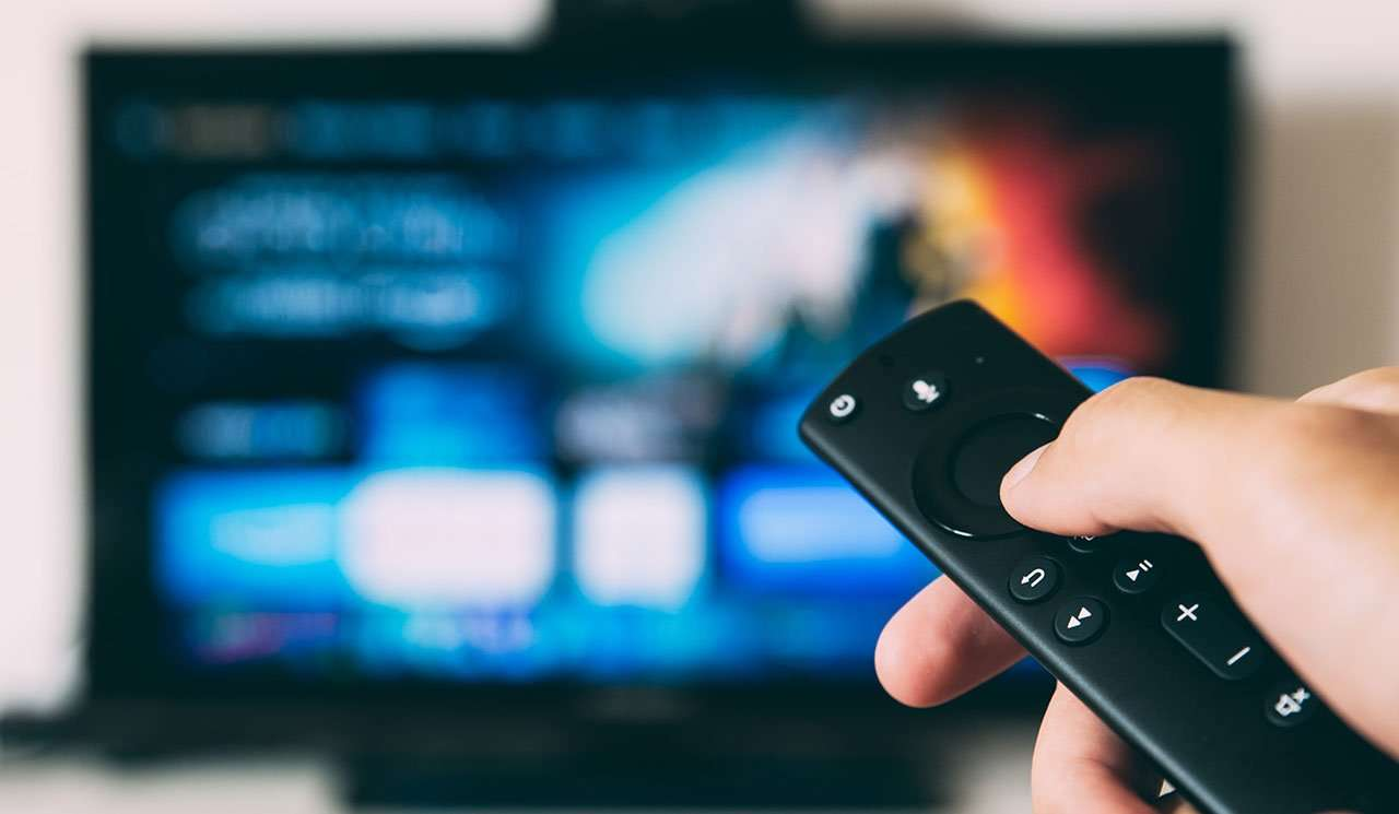 close up of person holding remote pointed at blurry tv